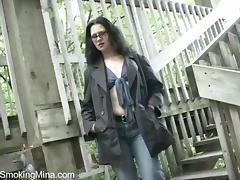 Brunette milf smokes and fingers her cunt on the stairs
